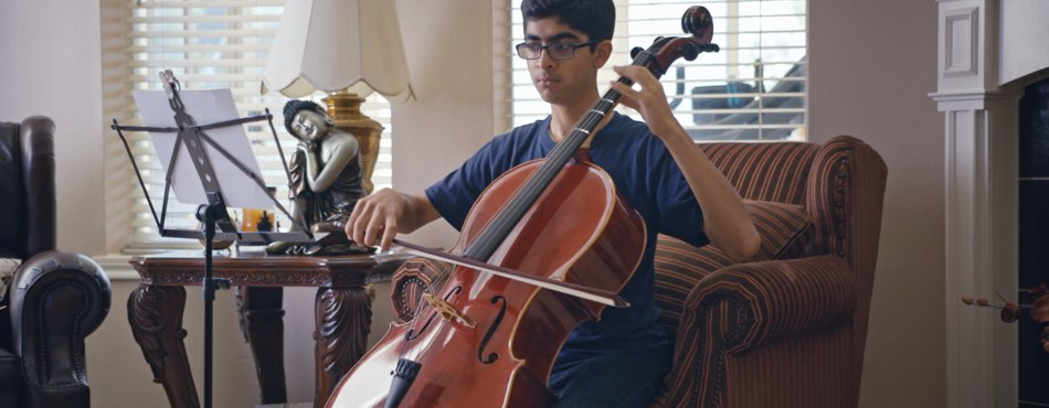 An advanced Kumon student plays the cello in his living room