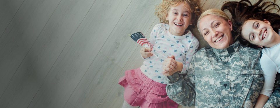 A veteran and her daughters lay smiling on a wooden floor