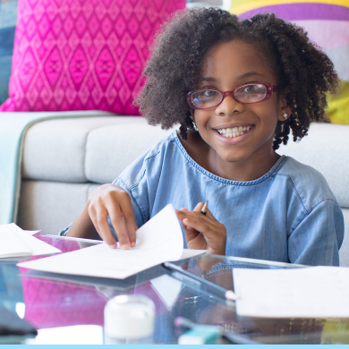 Girl smiling at the camera as she completes a Kumon Worksheet