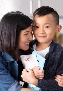 Mom smiling and hugging her son as he proudly holds a 100% Kumon Worksheet